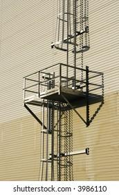 Enclosed metal ladder and platform on side of metal clad building.