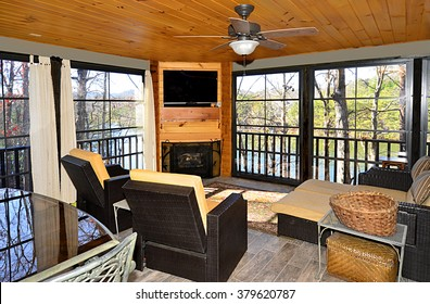 An enclosed porch area on a house overlooking a lake.