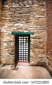 Enclosure inside old jail in Warrenton Virginia with prison door and high stone walls.