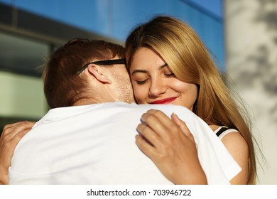 Encounter after travel or long separation. Charming young blonde woman hugging her unrecognizable boyfriend in sunglasses, holding him in gentle tender manner, closing eyes with enjoyment and pleasure