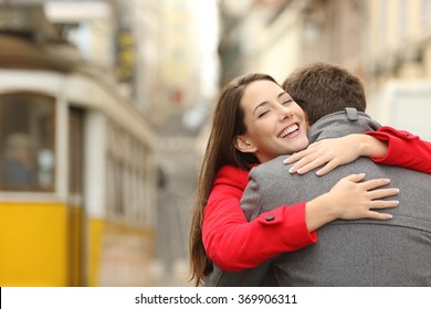 Encounter of a happy couple hugging in love in the street after a tram travel in a colorful scenery