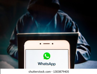 Encrypted instant messaging application WhatsApp logo is seen on an Android mobile device with a figure of hacker in the background.