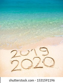 End of 2019 Happy New Year 2020, lettering on beach with wave and clear blue sea on sunny day. Handwritten inscription 2019 and 2020 on beautiful golden sand beach. New Years 2020 replace 2019 concept