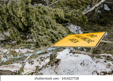 End avalanche are sign has fallen down because of the avalanche. Yellow sign laying on the ground.
