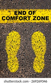 End of Comfort Zone message. Conceptual image with yellow paint footsteps on the road in front of horizontal line over asphalt stone background.