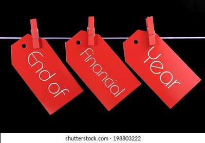 End of Financial Year red ticket sale tags hanging from pegs on a line against a black background.
