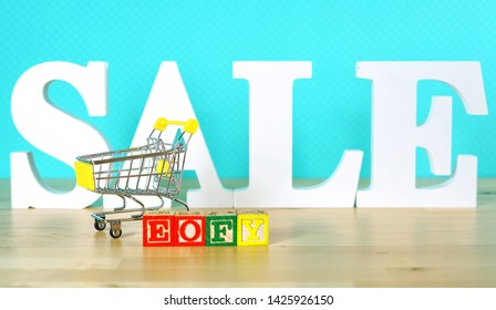 End of Financial Year sales shopping concept with mini shopping cart and large sale letters.