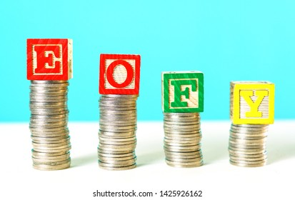 End of Financial Year and savings concept stacking coins with EOFY building blocks.
