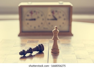 End game of chess with one fallen king figure.