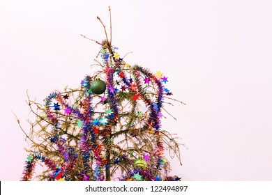 End of the holidays or other concept: dead fir Christmas tree with dried up needles; star garland and ornaments left in the tree.