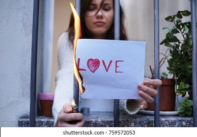 end of love story concept. disillusioned woman setting fire on a paper with the text love with heart symbol