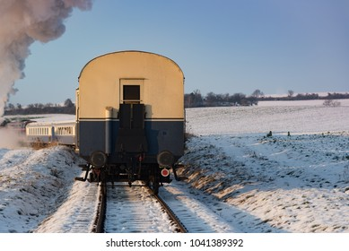 The end of a nostalgic steam train in Austria in the daytime on a clear day with snow on the ground.