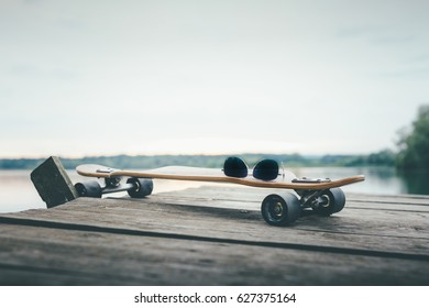 End part of wooden pier over the water surface with longboard and retro sunglasses on it. Image with very shallow depth of field-Focus on glasses. Suitable as background with large commercial space.