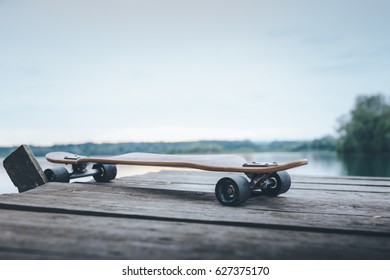 End part of wooden pier over the water surface with longboard. Image with very shallow depth of field - Focus on front truck of longboard. Suitable as background with large commercial space.