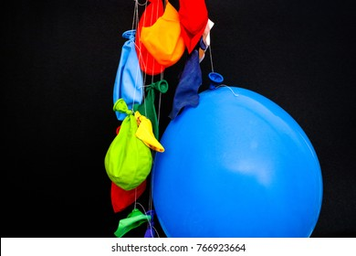End of a party. Some burst, deflated balloons and one inflated balloon hanging on threads. Black background.