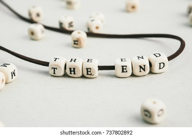 The end. phrase made of  wooden beads letters.  Horizontal composition. a series of conceptual phrases and words.