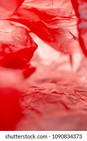 End Plastic Pollution. Abstract vibrant red background full frame inside plastic bag