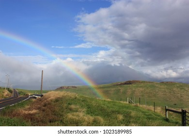 The end of the rainbow, dissolving into a grassy field next to the Kohala Mountain Road in North Kohala, Hawaii, USA