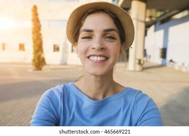 End result selfie picture of a beautiful young woman smiling, while wearing a hat and a blue tshirt on a sunset background