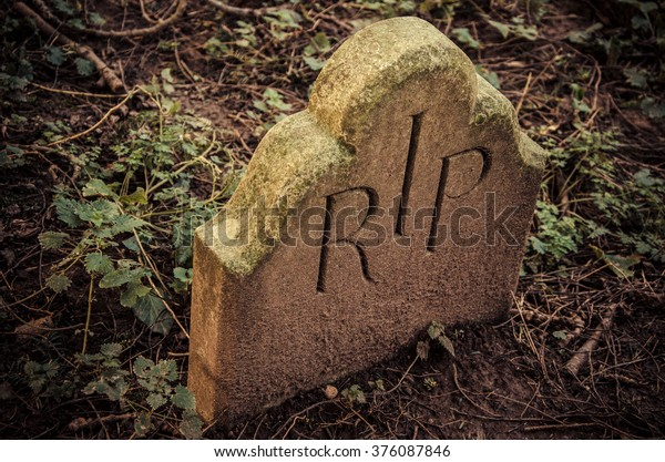 At the End - RIP engraved on tomb. Little tombstone with R.I.P inscription (Rest In Peace) in an old English graveyard.