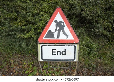 End of roadworks traffic sign leaning against hedge, UK