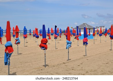 End of the season; rows of colorful sunshades, folded, on the beach at Deauville, France.