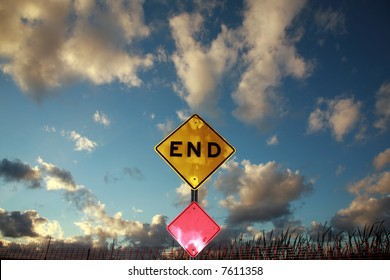 an End sign sits at the end of a road against a Blue Sky with Amazing fluffy clouds