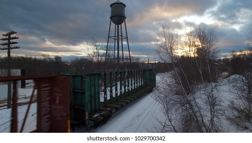 End of train next to water tower in winter with yellow sunset