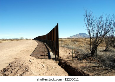 End of U.S.-Mexico border fence under construction in Arizona desert (U.S. to the left, Mexico to the right)