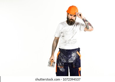 End of working day concept. Plasterer, repairman, foreman takes off helmet or hard hat, copy space. Bearded repairman with tired face and dirty shirt, holds plastering tool, white background.