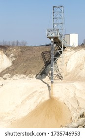 Ending part of working conveyor belt spills of sifted sand on the pile