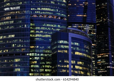 The endless array of windows of dark blue glass and glowing in the twilight purple steel frames forming the walls of modern office buildings.