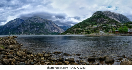 An endless chain of mountains reflecting itself in a calm water of Eidfjord. Taller parts of the mountains are partially covered with snow. Cloudy weather. Romantic landscape