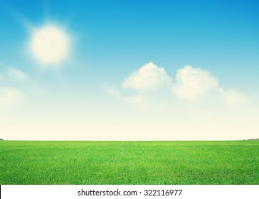 Endless green grass field and blue sky with clouds background