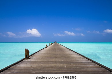 endless jetty to the horizon; view to a turquoise sea and blue sky with white clouds