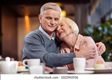 Endless love. Pensive joyful mature couple embracing while posing on the blurred background and woman closing eyes