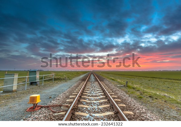 Endless railroad to the horizon under a blue and red sky as a concept for future career.
