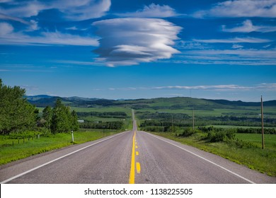 Endless road in Canada. A special cloud is hanging over the road. (Lenticular cloud)