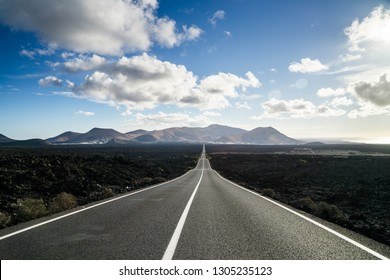 Endless road on a volcano in Timanfaya National Park in Lanzarote in the Canary Islands with a continuous line, black rocks on the side and volcanoes and clouds in the background