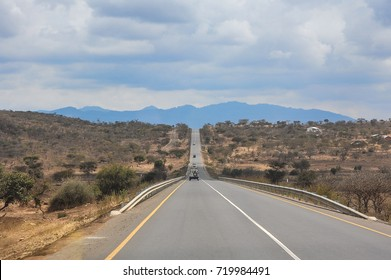 Endless road through dry, dusty landscape between Kenya and Tanzania, East Africa