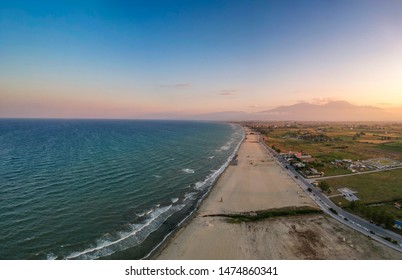 The endless sandy beach over seaside town Paralia Katerini - Aerial panorama over the Olympic Coast in Pieria, Central Macedonia, Greece at sunset.