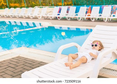 Endless summer. Cute baby relaxing at sunbed near pool at hawaii, hotel. Lttle girl wearing sunglasses. Fashion child sunbathing