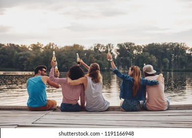 To endless summer! Rear view of young people in casual wear toasting with a beer bottles while sitting on the pier
