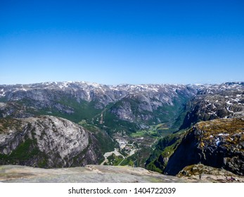 An endless vie on fjords around famous Kjerag, Rogaland, Norway. Tops of the mountains covered with snow, lower part are already in blossom. Steep and dangerous mountains. Beautiful and bright day