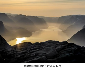 Endless view on Lysefjorden seen from Preikestolen, Pulpit Rock, Norway during soft sunset. Sunbeams reflecting in the water. Steep cliffs join the water. Barren rocks on the top of the cliffs.