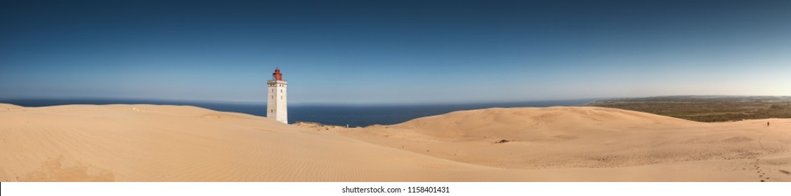 Endless white sand dunes and the famous danish lighthouse landmark during daytime and blue sky in summer vacation. Rubjerg Knude Lighthouse, Lønstrup in North Jutland in Denmark, Skagerrak, North Sea