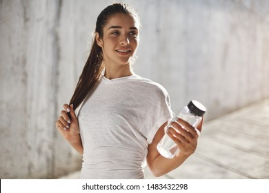 Endurance, sport and fitness concept. Alluring young sporty brunette woman in white t-shirt, hold glass water bottle, smiling satisfied after running few laps around neighbourhood, morning jogging