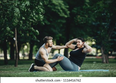 Endurance training, sport, weight loss, teamwork and healthy lifestyle concept. Plus size woman working out with personal trainer. Fitness instructor support, abdominal crunches, fat burning exercises