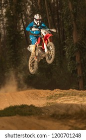 Enduro bike rider in action. Jump on sandy terrain.