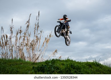 Enduro bike rider in action. Jump on mud and grass terrain.